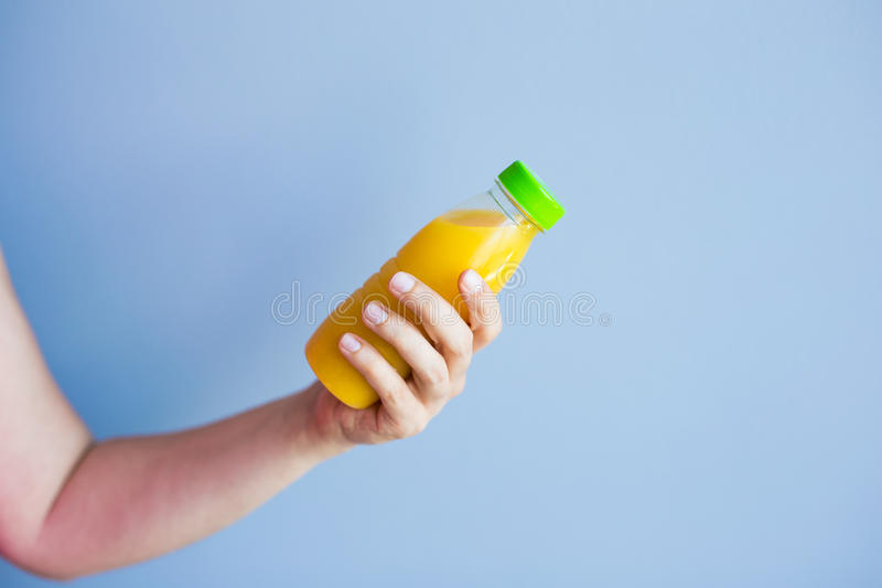 Primer de la mano femenina que sostiene una botella con el jugo imagen de archivo libre de regalías