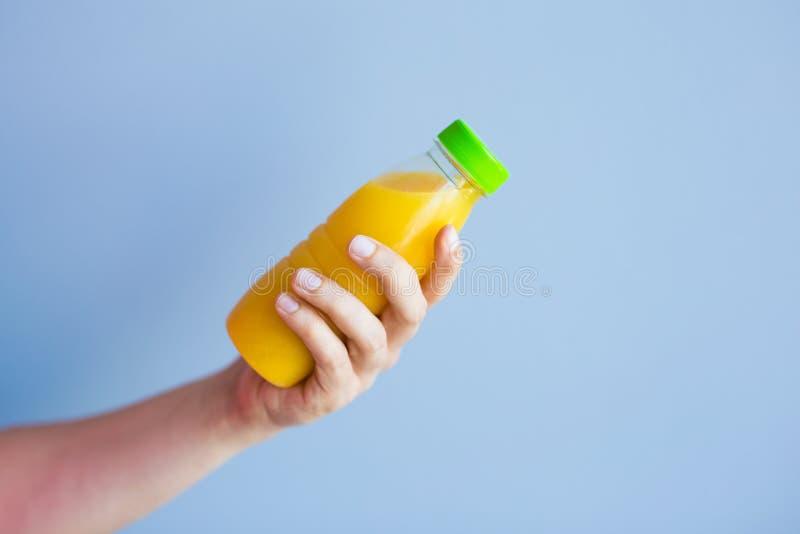Primer de la mano femenina que sostiene una botella con el jugo foto de archivo libre de regalías