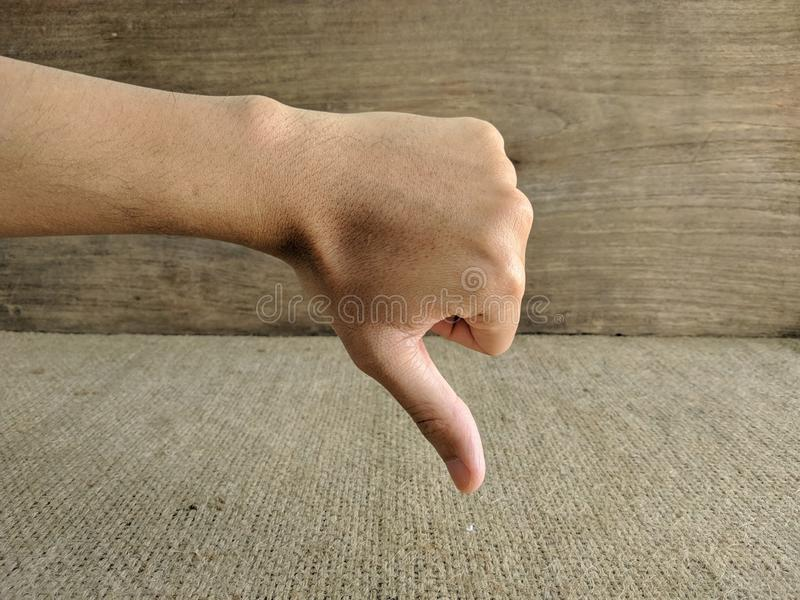 Primer de la mano masculina que muestra los pulgares abajo de la muestra fotografía de archivo