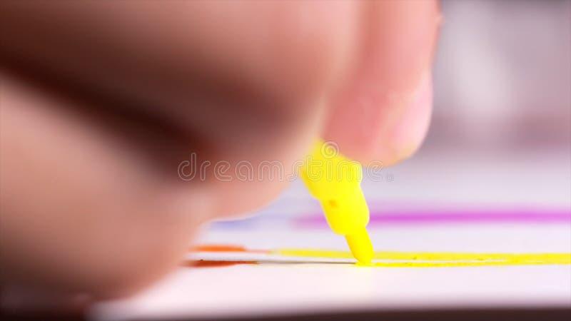 Primer de la mano de la mujer con la pluma sentida amarilla que dibuja una cierta figura en la hoja de papel en la tabla acci?n c fotos de archivo