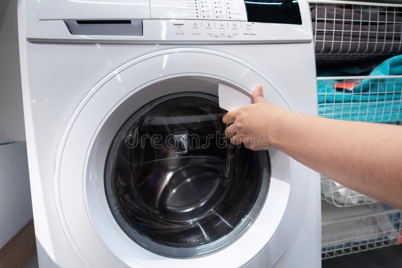 Primer de la mano de la mujer mientras que abre una puerta de la lavadora, concepto de la forma de vida de la economía doméstica imagen de archivo