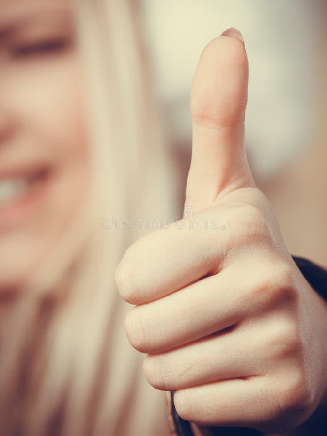 Primer de la mano de la mujer que muestra el pulgar para arriba imagen de archivo