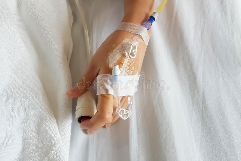 Primer de la mano paciente con la aguja e IV de la infusi?n tubo para la infusi?n intravenosa que empuja el bot?n de la emergenci fotografía de archivo