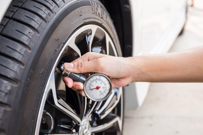 Primer de la mano que sostiene el indicador de presión para el neumático del coche imágenes de archivo libres de regalías