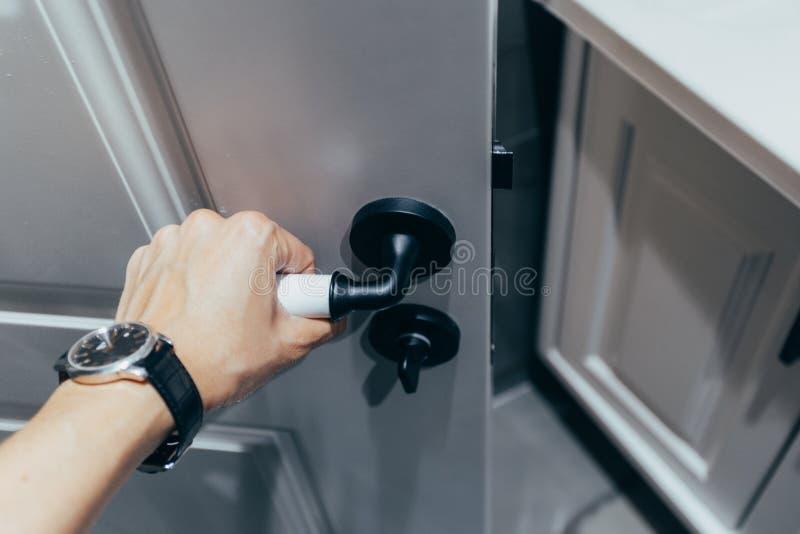 Primer de la mano que sostiene el tirador del metal en puerta de madera imagen de archivo libre de regalías