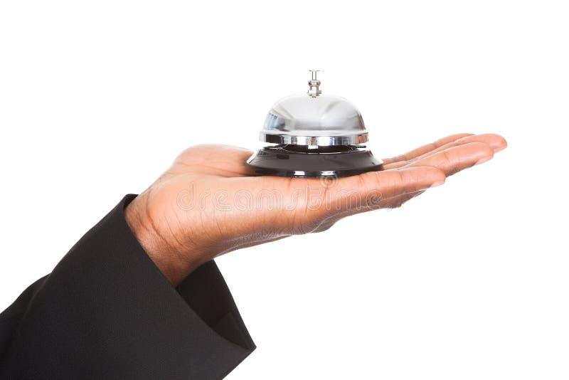 Primer de la mano que sostiene la campana del servicio fotos de archivo libres de regalías