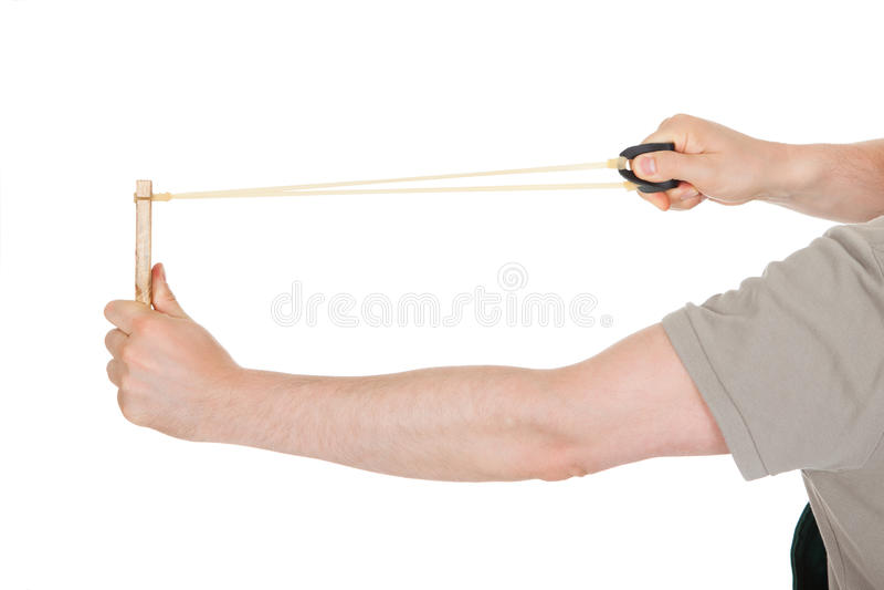Primer de la mano que tira del tiro de honda imagenes de archivo