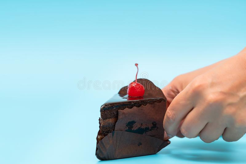 Primer de la mano que toma un pedazo de torta de chocolate foto de archivo
