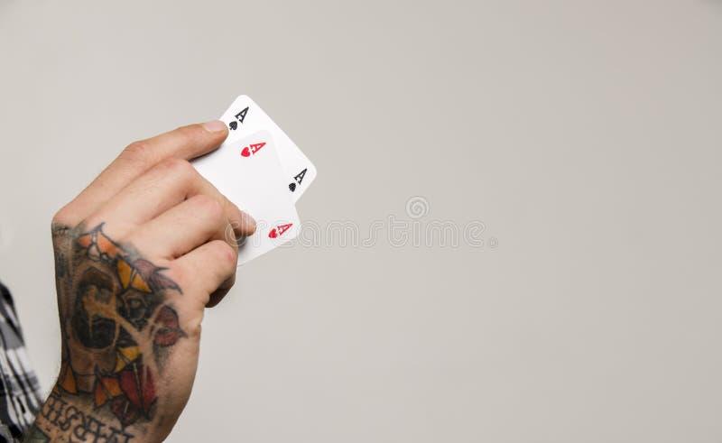 Primer de la mano tatuada que sostiene dos as imágenes de archivo libres de regalías