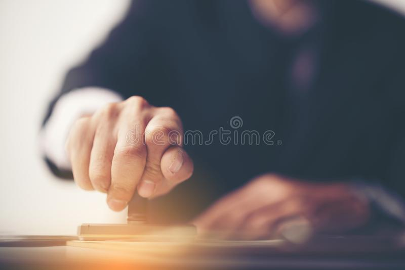 Primer de la mano de una persona que sella con el sello aprobado en Docu imágenes de archivo libres de regalías