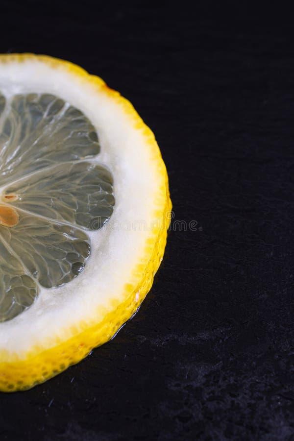 Primer de la media rebanada de limón en fondo de piedra negro mojado fotografía de archivo