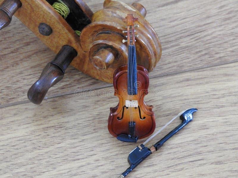 Primer de la miniatura de un violín con el arco apoyado para arriba en un violín del mismo tamaño fotos de archivo