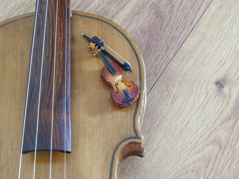 Primer de la miniatura de un violín con el arco en un violín del mismo tamaño imagen de archivo libre de regalías