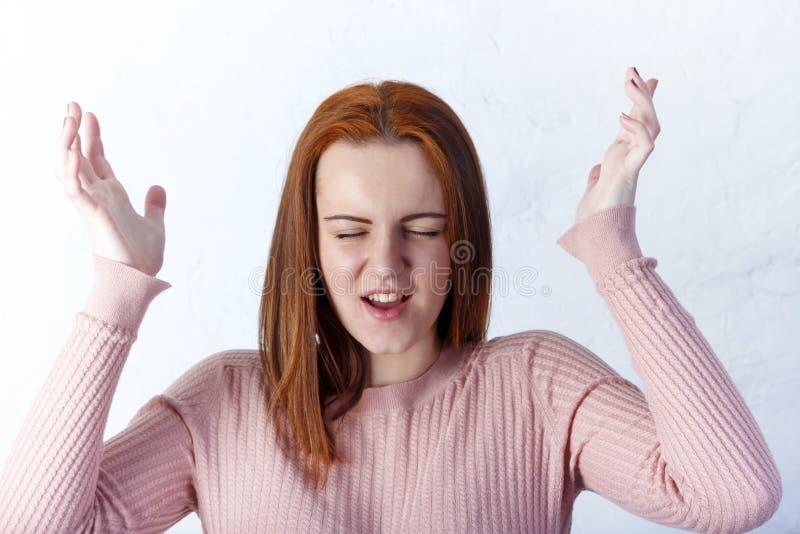 Primer de la muchacha bonita infeliz desconcertada aislada en el fondo blanco que muestra emociones negativas imagen de archivo libre de regalías