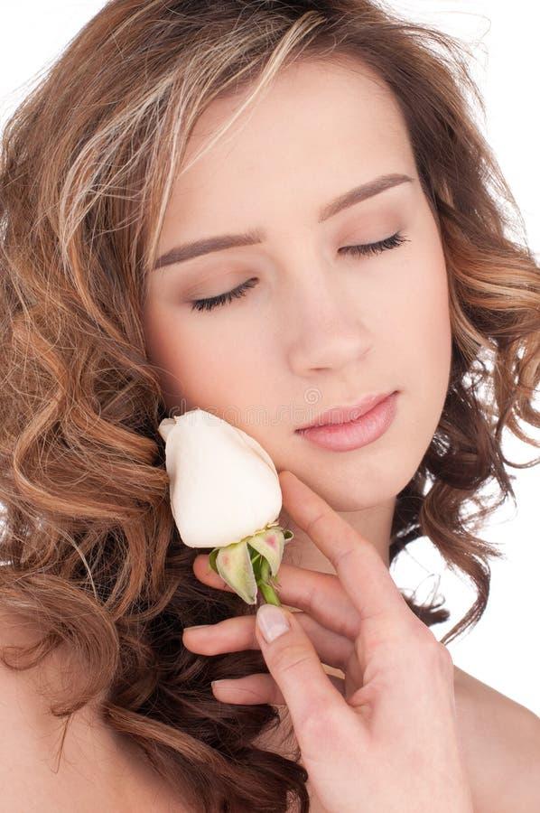 Primer de la muchacha hermosa con la flor color de rosa del blanco foto de archivo