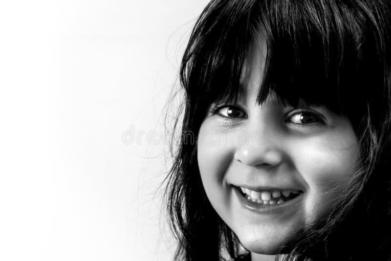 Primer de la muchacha linda del pequeño niño que mira la cámara con una sonrisa grande y optimista fotografía de archivo