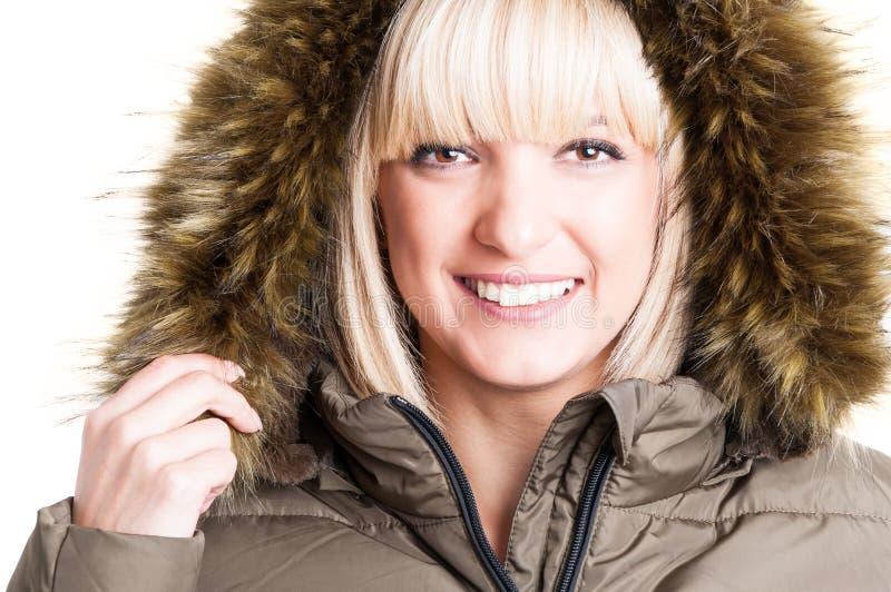 Primer de la muchacha linda que sostiene la capilla peluda del invierno fotografía de archivo libre de regalías