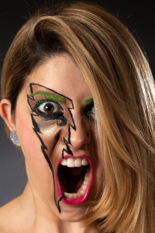 Primer de la muchacha que grita con maquillaje del relámpago fotos de archivo libres de regalías