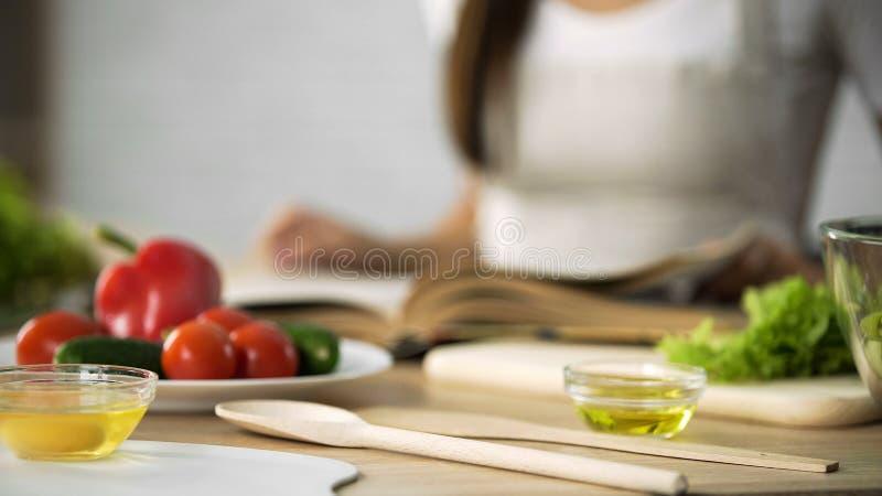 Primer de la muchacha que mueve de un tirón con cocinar las páginas del libro, eligiendo receta de la ensalada imagen de archivo libre de regalías