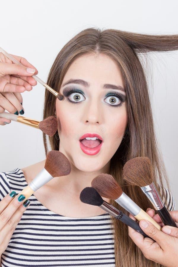 Primer de la muchacha rubia hermosa que consigue maquillaje fotos de archivo libres de regalías