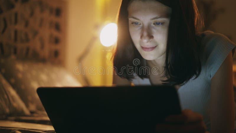 Primer de la mujer atractiva joven que usa la tableta en la noche que miente en cama en casa foto de archivo libre de regalías