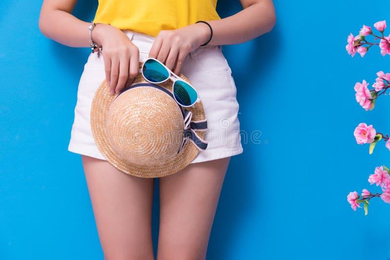 Primer de la mujer de la belleza que presenta con las gafas de sol y el sombrero de paja delante del fondo azul de la pared Veran foto de archivo