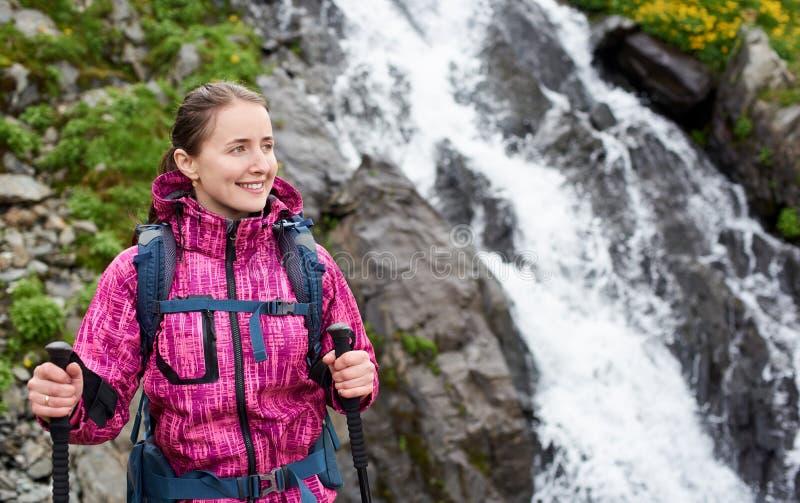 Primer de la mujer bonita contra la cascada Balea en las montañas de Fagarash imágenes de archivo libres de regalías