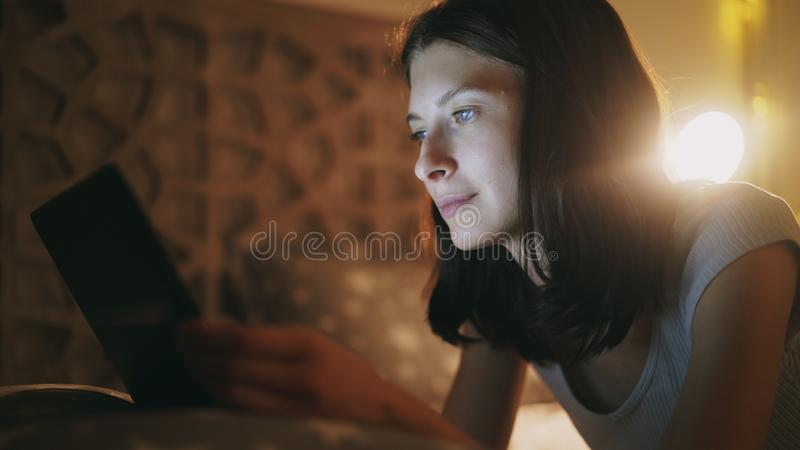 Primer de la mujer bonita joven que usa la tableta en la noche que miente en cama en casa foto de archivo libre de regalías