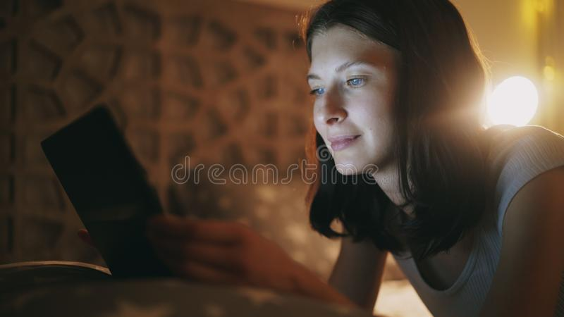Primer de la mujer bonita joven que usa la tableta en la noche que miente en cama en casa imagen de archivo libre de regalías