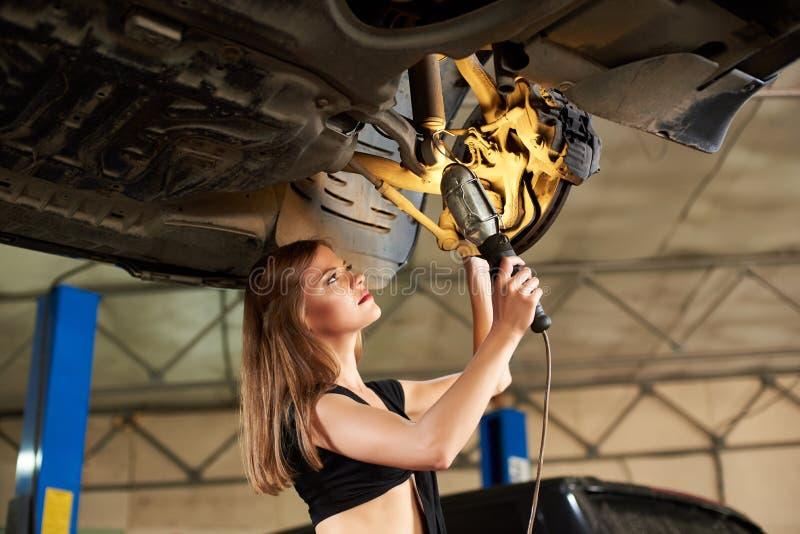Primer de la mujer con la linterna que examina el coche en la elevación hidráulica fotografía de archivo libre de regalías