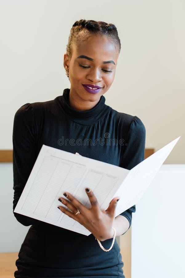 Primer de la mujer de negocios elegante sonriente que lleva el vestido negro en la oficina ligera que escribe su orden del día foto de archivo libre de regalías