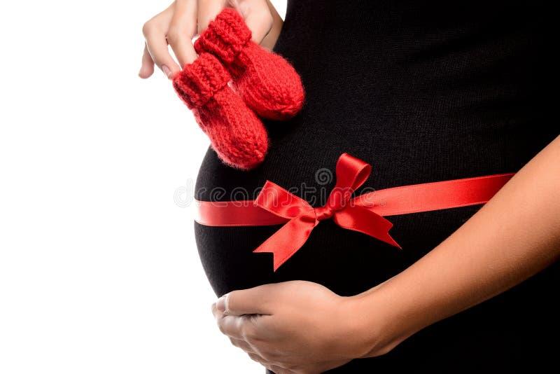 Primer de la mujer embarazada con los botines del bebé foto de archivo libre de regalías