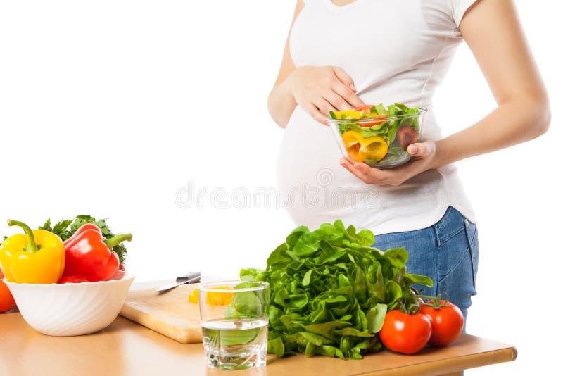 Primer de la mujer embarazada que sostiene el cuenco con las verduras frescas imágenes de archivo libres de regalías