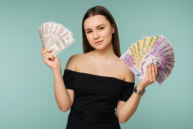 Primer de la mujer feliz joven que sostiene dos fans de las cuentas del dólar y del euro, mirando la cámara, aislada en fondo azu fotos de archivo
