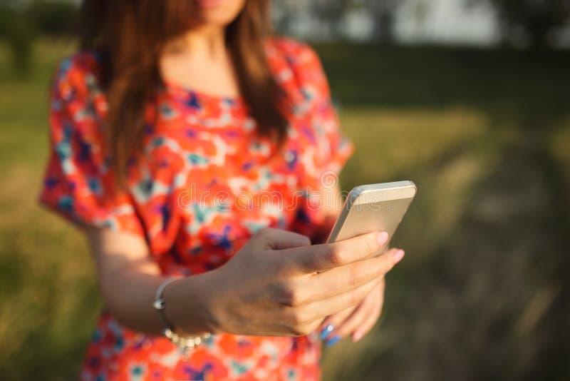 Primer de la mujer joven en vestido rojo usando el teléfono elegante móvil foto de archivo libre de regalías