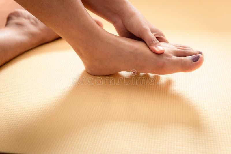 Primer de la mujer joven que da masajes a sus pies, concepto de la atención sanitaria foto de archivo