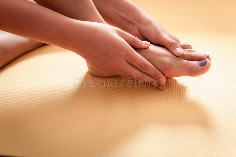 Primer de la mujer joven que da masajes a sus pies, concepto de la atención sanitaria imagenes de archivo