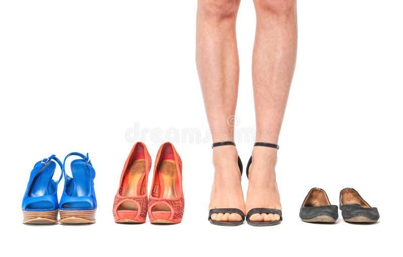 Primer de la mujer que elige un par de zapatos - aislados en blanco imagen de archivo libre de regalías