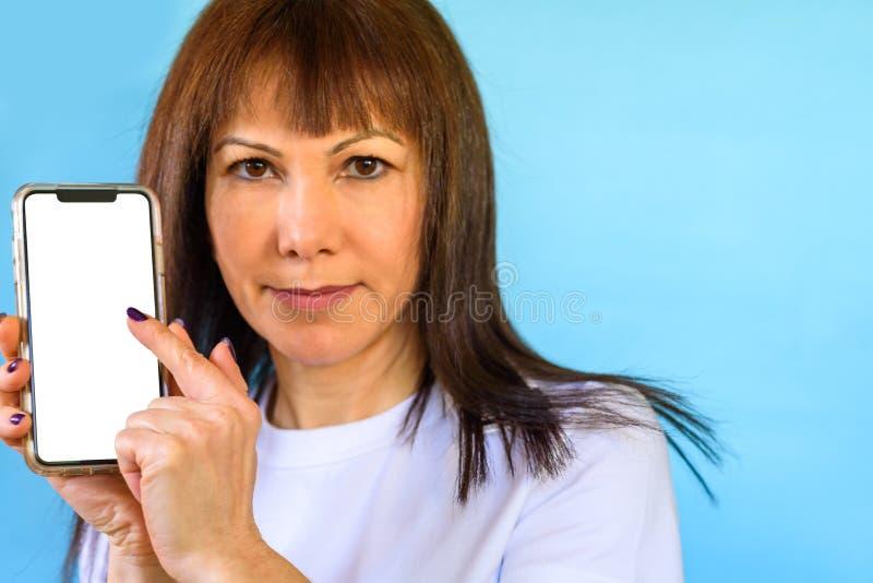 Primer de la mujer que usa smartphone Mofa encima de la pantalla en blanco del color blanco del teléfono móvil foto de archivo