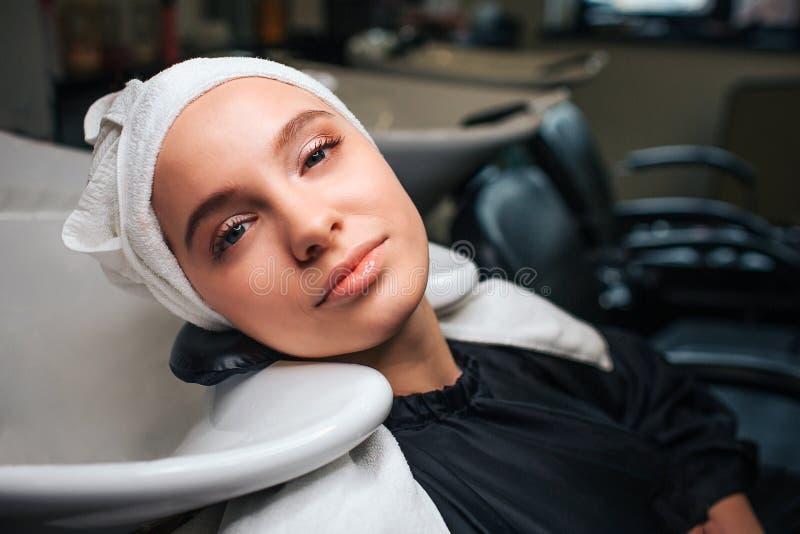 Primer de la mujer relajada hermosa con la toalla en la cabeza que mira la cámara después del lavado profesional del pelo Cuidado imagenes de archivo