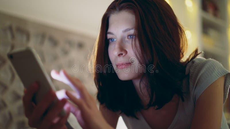 Primer de la mujer sonriente joven que usa el smartphone que miente en cama en casa en la noche imagen de archivo libre de regalías
