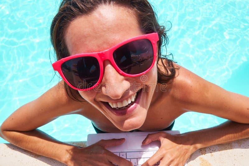 Primer de la mujer sonriente que usa el ordenador portátil en el poolside fotos de archivo