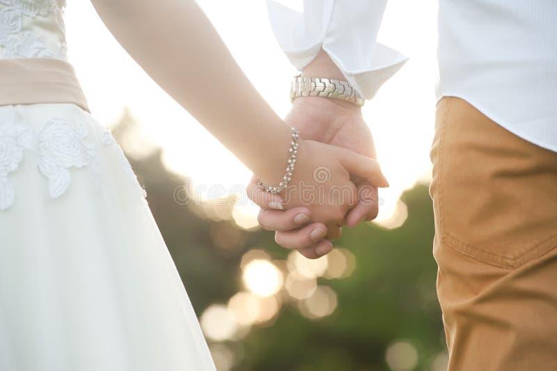Primer de la novia y del novio que llevan a cabo las manos fotografía de archivo