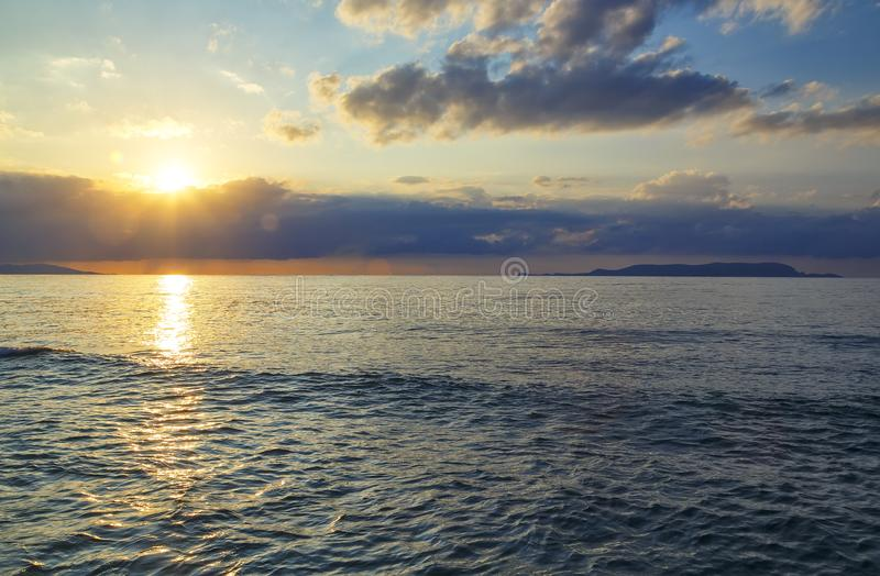 Primer de la onda del mar en el tiempo de la puesta del sol con la reflexión roja y anaranjada del sol en el agua Fondo enmascara imágenes de archivo libres de regalías