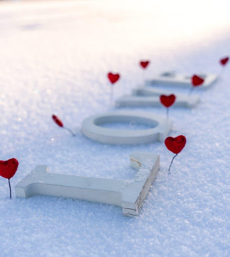 Primer de la palabra aislada y de x22; Love& x22; de pedazos de madera en la nieve en Sunny Winter Day con el fondo blanco con el fotografía de archivo libre de regalías