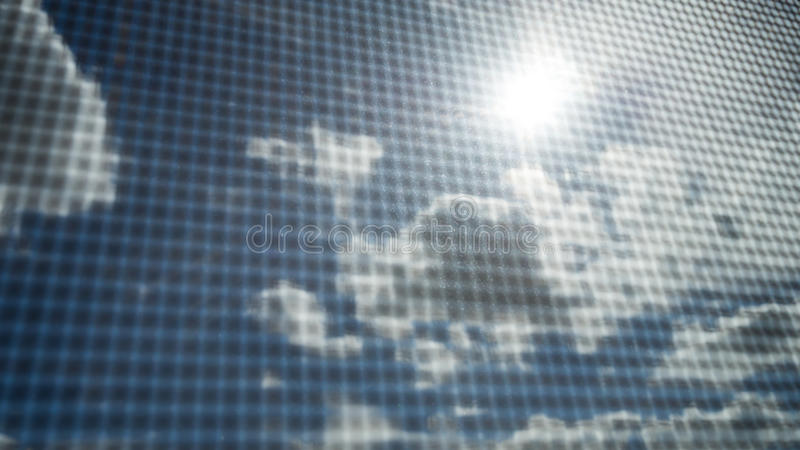 Primer de la pantalla de alambre del mosquito con el rayo del sol en el cielo azul y las nubes blancas en fondo foto de archivo libre de regalías