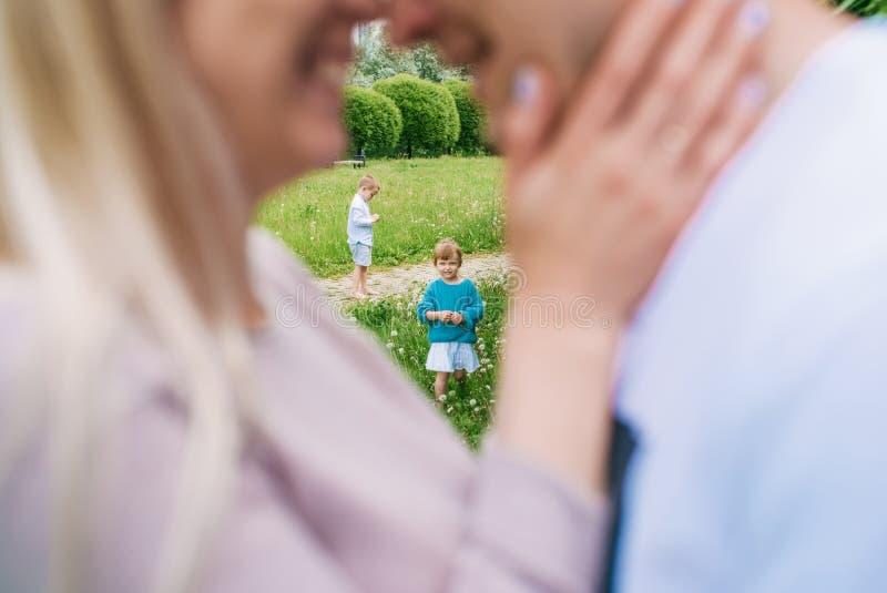 Primer de la pareja feliz con sus pequeños niños que se besan sobre un fondo del parque Foco en ni?os foto de archivo