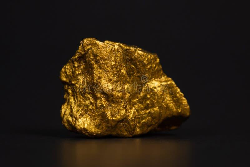 Primer de la pepita de oro o mineral del oro en fondo negro, muy imagen de archivo libre de regalías