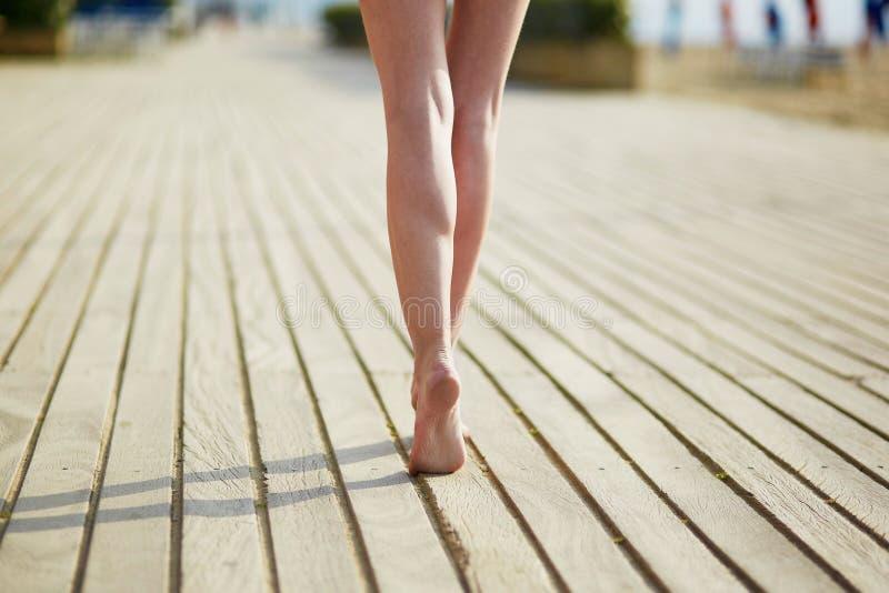 Primer de la pierna hermosa de la mujer en el embarcadero de madera de la playa imagen de archivo