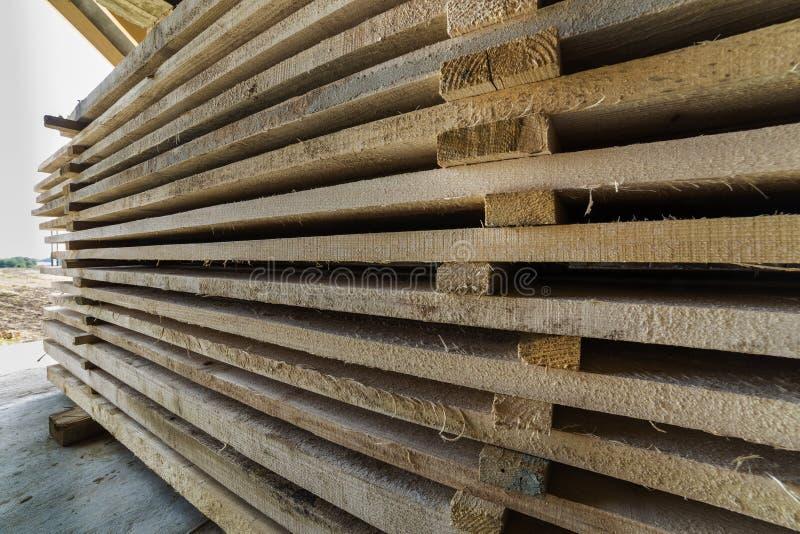 Primer de la pila cuidadosamente llenada de tableros de madera ásperos desiguales marrones naturales dentro del sitio del ático b foto de archivo